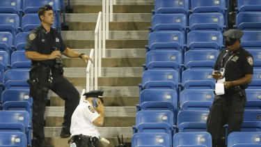 Police officers stand beside a drone that crashed into an empty section of seats at the US Open tennis tournament at Flushing Meadows, New York.