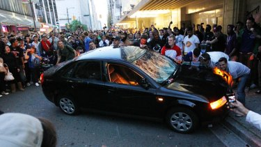 Rioters burn police cars.