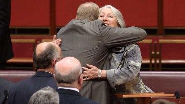 Senator Sue Boyce is hugged by Senator Ian Macdonald after she gave her valedictory speech. Photo: Andrew Meares