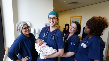 Nurse/midwife, Cameron Littlewood at Westmead Hospital holding one-day-old Lilian, with his colleagues , Sabah Scheiwani, Caragh Myers and Catherine Seay.