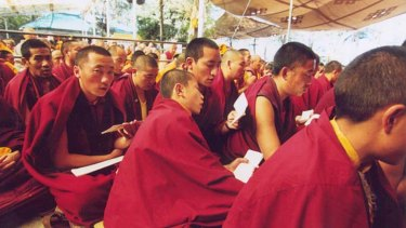Monks chant prayers before the beginning of the day's teachings from the Dalai Lama.