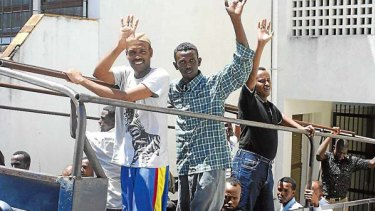 Suspected pirates gesture as they leave court in Kenya on Tuesday, November 9, 2010. A judge freed them because their alleged raid took place off the Somali coast outside Kenyan jurisdiction.