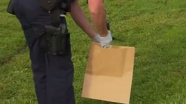 A police officer picks up a knife outside a Norlane house, where a man was stabbed to death.