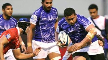 Sakaria Taulafo of Samoa runs through a tackle by  Viliami Faingaa of Tonga.