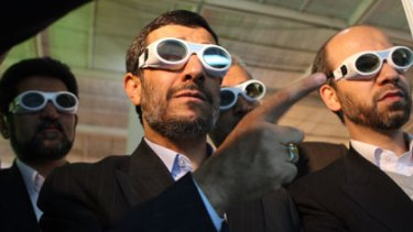 Giving them the finger ... the Iranian President, Mahmoud Ahmadinejad, at a laser exhibition on Sunday, appears to have reneged on a UN-drafted nuclear deal.