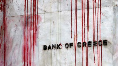 A branch of the Bank of Greece is seen stained with red paint thrown by demonstrators during a protest in central Athens.