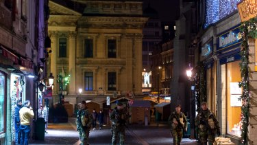 Armed soldiers patrol along Rue des Sols in Brussels on Monday.