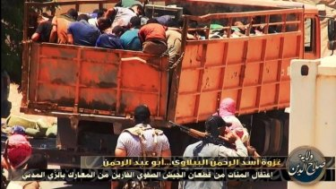 ISIL prisoners are packed into a truck and driven away.