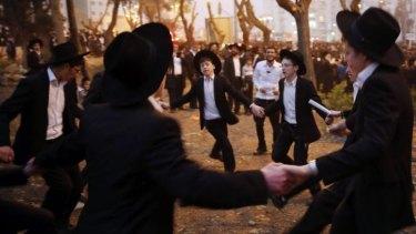 Ultra-Orthodox Jewish youths dance after a mass prayer at the Jerusalem demonstration.