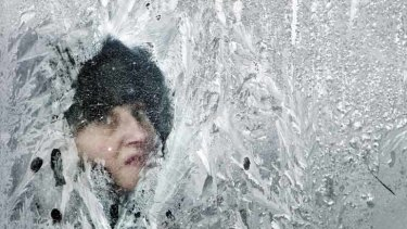 Death toll from deep freeze rises... a woman looks out of a window covered in frost on a bus in Bucharest, Romania.