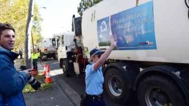 Police guide garbage trucks from Blacktown at the protest against SBS show <i>Struggle Street</i>.