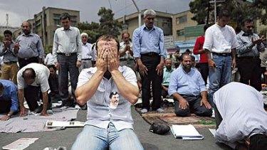 Word on the street ... men pray after listening to Supreme Leader Ayatollah Khamenei's sermon at Tehran University.