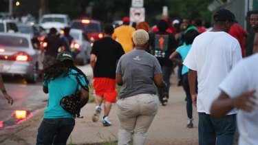 People flee as police advance on protestors firing tear gas and rubber bullets to force them from the business district into nearby neighbourhoods in Ferguson, Missouri.