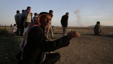 Watching brief: Turkish Kurds watch as airstrikes hit Kobane.
