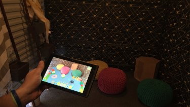 A corner full of colourful cushions comes to life with interactive virtual toys on the screen.
