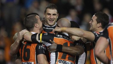 Robbie Farah celebrates with Tigers team mates after kicking the golden point field goal against the Knights.
