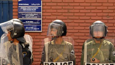 Tension ... Iranian riot police stand guard at the British embassy in Tehran as countries engage in tit-for-tat expulsions.