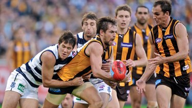 Gotcha: Hawthorn's Luke Hodge is tackled by Andrew Mackie at the MCG.
