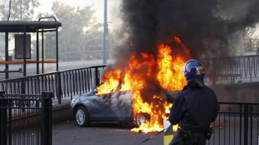 Riots spreading ... a policeman and his dog walk towards a burning car in central Birmingham,.
