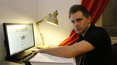 Austrian student Max Schrems sits with 1222 pages worth of his personal data that Facebook provided to him.