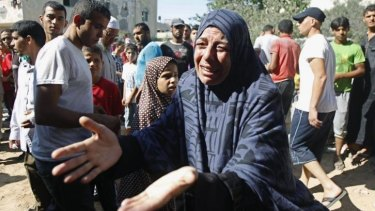 A Palestinian woman outside her home after a deadly strike on her house.