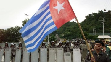 This file photo shows a West Papuan separatist carrying the banned Morning Star flag as he walks past a line of Indonesian riot police officers surrounding a pro-independence celebration in Jayapura, Irian Jaya.