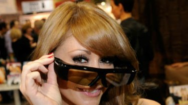 Adult film actress Monique Alexander displays polarized 3D glasses at the Funky Monkey Movies booth at the 2011 AVN Adult Entertainment Expo.