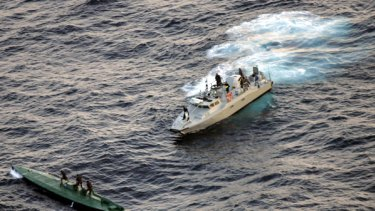 Mexican navy sailors ride on top of a seized drug smuggling submarine.