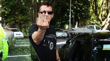 """""""He's not the Phil we've known"""": AC/DC drummer Phil Rudd gestures after appearing in Tauranga District Court charged with threatening to kill and possession of meth and marijuana in November."""