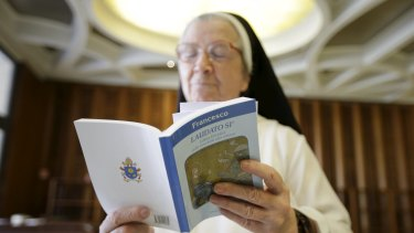 A nun reads Pope Francis' new encyclical titled 'Laudato si', the first papal document dedicated to the environment, at the Vatican on Thursday.