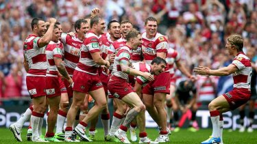 Wigan Warriors players celebrate winning the Challenge Cup final.