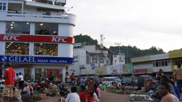Indigenous traders sell produce in Jayapura, where migrants own many businesses.