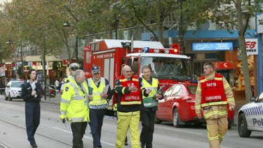 Police and fire officers in Swanston Street after fumes caused evacuations in the city.