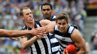 Geelong's Tom Hawkins tries to break a tackle by Collingwood's Nick Maxwell.