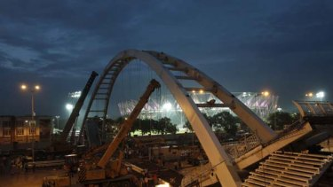 Glitz and squalor  ... cranes work on Delhi's collapsed footbridge.