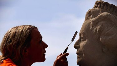 Touch up … artist Nicola Wood sculpts the Queen in sand.