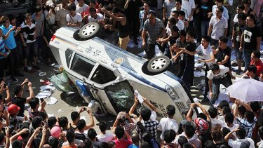 Riots ... demonstrators clash with police in Qidong.