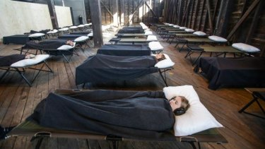 In another Marina Abramovic event, participants are tucked into bed in what feels like an austere school camp.