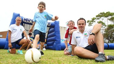 Emphasis on fun … a Marrickville Public School pupil with, from left, Matildas striker Kyah Simon, the head of the AFDP, Urs Zanitti, and Mr Soccer's Mark Robertson.