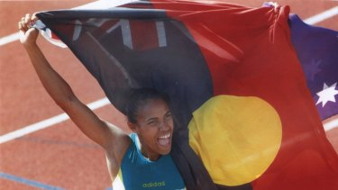 Cathy Freeman holds up the Aboriginal flag alongside the Australian flag after her 400m win at the 1994 Commonwealth Games.