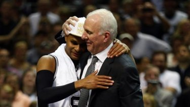 Patty Mills with San Antonio Spurs coach Gregg Popovich. Mills is expected to miss seven months after tearing the rotator cuff in his shoulder.
