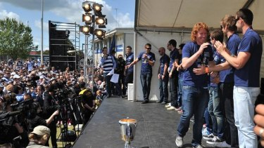 Cat walks ... Geelong skipper Cameron Ling strolls past his teammates with a grin at yesterday's family day celebration after the grand final win.