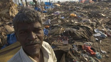 A fisherman stands amid the wreckage of the hut he used to occupy at Pattanambakam in Chennai, India on Sunday January 2, 2005.