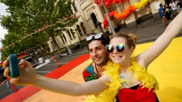 Joshua Burge and Natalia Quesnel from Spain pose for a selfie in Lygon Street.