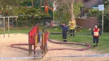 Investigators examine the Copacabana playground where the sand-blower was operating.