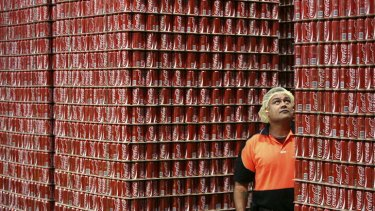 An employee inspects skids of Coca-Cola soft-drink ready for dispatch from the Coca-Cola Amatil bottling plant in Sydney, Australia.