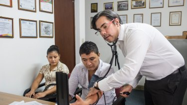 Dr Ramon Garcia-Trabanino talks with patients in his clinic in El Salvador'€™s capital, San Salvador.