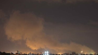 Retaliation ... a plume of smoke rises above Gaza City as Israeli air strikes hit.