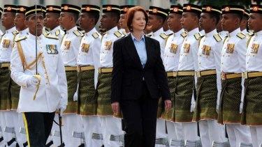 Heartless plan ...  Julia Gillard inspects a guard of honour in Malaysia.