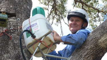 Gunnedah farmer Robert Frend refills a Blinky Drinker he designed to helps keep koalas hyrdrated.